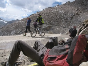 Samantha Gash on her way to Leh from Khardung La; a member of her team keeps company on a bicycle. Watching on are BRO workers enjoying a break (Photo: Shyam G Menon)